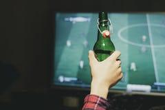 Le football de observation d'homme à la maison pendant la nuit et la bière potable f photographie stock libre de droits