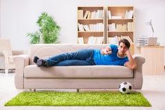 Le football de observation d'homme à la maison se reposant dans le divan images stock