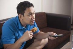 Le football de observation d'homme asiatique ? la TV images libres de droits