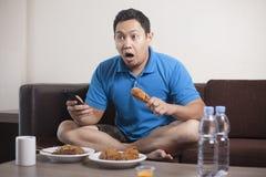 Le football de observation d'homme asiatique ? la TV image stock
