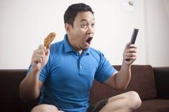 Le football de observation d'homme asiatique ? la TV images stock