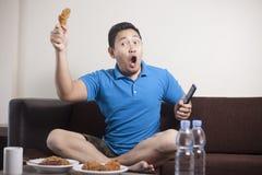 Le football de observation d'homme asiatique ? la TV photo stock