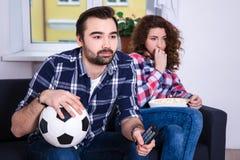 Le football de observation d'homme avec son amie ennuyée Photographie stock libre de droits