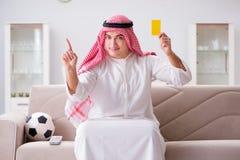 Le football de observation de jeune homme arabe se reposant sur le sofa Photographie stock