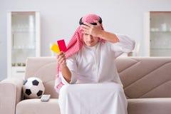 Le football de observation de jeune homme arabe se reposant sur le sofa Photographie stock libre de droits