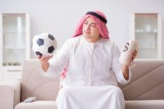 Le football de observation de jeune homme arabe se reposant sur le sofa Images stock