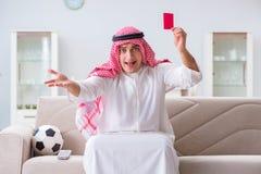 Le football de observation de sport d'homme arabe à la TV Photographie stock libre de droits