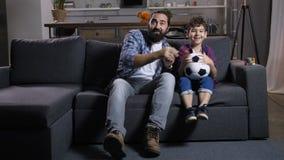 Le football de observation enthousiaste de papa et de fils à la TV à la maison banque de vidéos