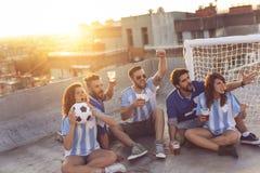 Le football de observation et bière potable Photos stock