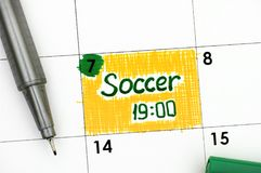 Le football 19-00 de rappel dans le calendrier avec le stylo vert Image stock