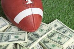 Le football de style d'université sur le champ avec une pile d'argent Photographie stock