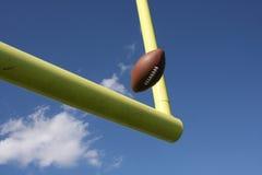 Le football donné un coup de pied par les montants Image libre de droits