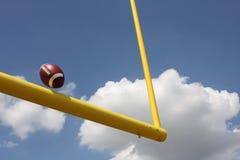Le football donné un coup de pied par les poteaux image libre de droits