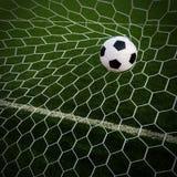 Le football du football dans le filet de but avec le champ d'herbe verte Photographie stock libre de droits