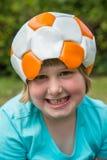 Le football en cuir de port de jeune fille sur la tête Photographie stock libre de droits