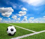 Le football et le terrain de football engazonnent le fond de ciel bleu de stade Photographie stock libre de droits