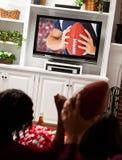Le football : Les fans encouragent pour le jeu à la télévision Image stock