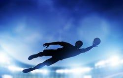 Le football, match de football. Un gardien de but sautant enregistrant la boule du but Photos stock