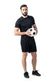Le football sûr du joueur futsal tenant la boule avec le regard audacieux à l'appareil-photo photo libre de droits