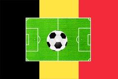 Le football sur le fond du champ et le drapeau de la Belgique Photographie stock libre de droits