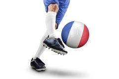 Le footballeur donne un coup de pied la boule avec un drapeau de Frances Photos stock