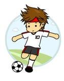 Le footballeur du numéro 10 essaye de donner un coup de pied la bille Images stock