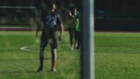Le footballeur fonctionne, frappe la boule et manque après le filet, brouillé pour le fond banque de vidéos