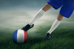 Le footballeur s'exerce pour donner un coup de pied une boule le champ Images stock