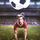 Le footballeur sautant pour un en-tête sur le champ de fotball images libres de droits