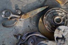 Le forbici arrugginite del metallo d'annata si trovano su asfalto, vicino alla ruota del metallo ed ai vecchi stracci, natura mor Fotografie Stock