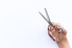 Le forbici dei capelli nell'isolato delle mani su fondo Immagine Stock