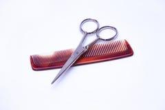 Le forbici ed il pettine dei parrucchieri su un fondo bianco Fotografia Stock