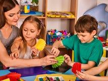 Le forbici prescolari in bambini passano la carta di colore di taglio con l'insegnante Fotografia Stock Libera da Diritti
