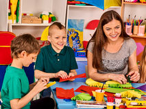 Le forbici prescolari in bambini passano la carta di taglio con l'insegnante nella classe Immagine Stock Libera da Diritti