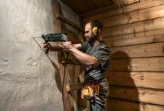 Le foret de travailleur de la construction perforent le mur en béton photos stock