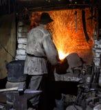 Le forgeron évente un four brûlant Image stock