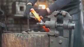 Le forgeron forgeant manuellement dans la forge Photographie stock