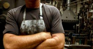Le forgeron se tenant avec des bras a croisé dans l'atelier 4k clips vidéos