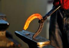 Le forgeron tient un fer à cheval chaud de grésillement Images stock