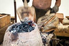 Le forgeron traditionnel emploie des soufflets pour garder un feu Photos stock