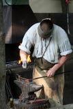 Le forgeron travaille avec des outils sur l'enclume Photos stock