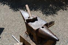 Le forgeron travaille le fer avec l'enclume et le marteau images libres de droits