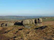 Le formazioni rocciose nei bridestones attraccano in West Yorkshire con una vista panoramica sopra la campagna della pennina fotografia stock libera da diritti