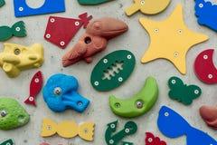 le forme 3D e le icone su una parete, alcune con la mano rampicante tiene Fotografie Stock Libere da Diritti