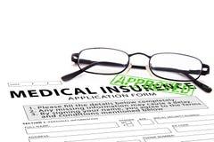 Le formulaire de demande d'assurance-maladie avec le vert a approuvé le timbre Image stock