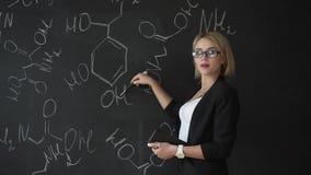 Le formule di scrittura dell'insegnante sul bordo di gesso e spiega gli studenti la formula archivi video