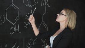Le formule di scrittura dell'insegnante sul bordo di gesso e spiega gli studenti la formula video d archivio