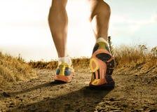 Le forti gambe e scarpe dello sport equipaggiano pareggiare nell'allenamento di addestramento di forma fisica fuori dalla strada Fotografie Stock