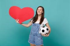 Le fotbollsfanjubel för ung kvinna stötta upp det favorit- laget med fotbollbollen, tom tom röd hjärta som isoleras på blått royaltyfri foto