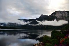Le foto della montagna e del lago con la mattina annebbiano sopra il lago in Hallstatt dell'Austria Fotografia Stock